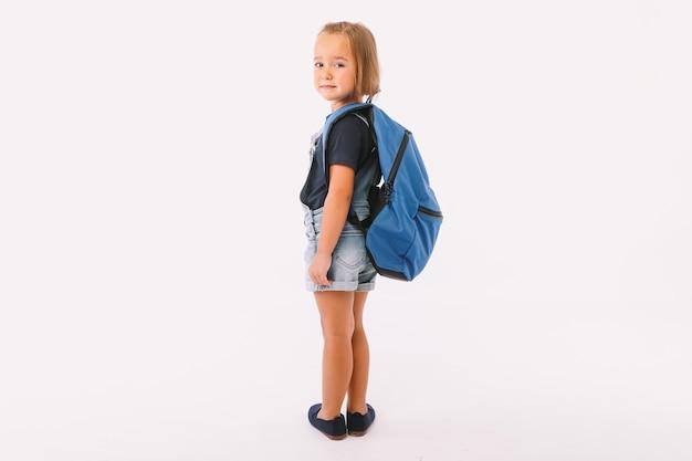 Petite fille aux cheveux blonds vêtue d'une salopette en jean et d'un t-shirt bleu, avec un sac à dos prêt pour la rentrée, de son côté, sur fond blanc
