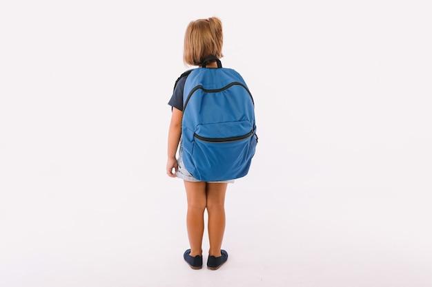 Petite fille aux cheveux blonds vêtue d'une salopette en jean et d'un t-shirt bleu, avec un sac à dos prêt à retourner à l'école, le dos tourné, sur fond blanc