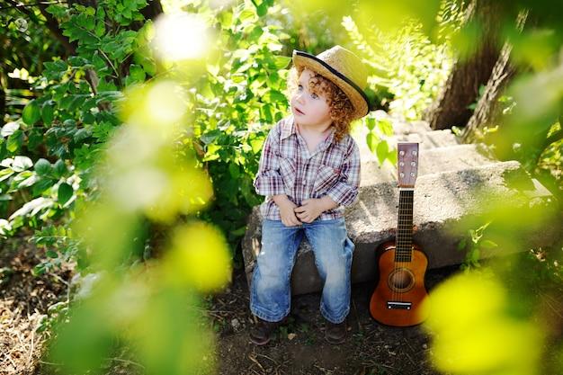 Petite fille aux cheveux bouclé roux assis avec une guitare dans le parc