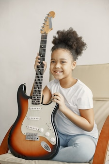 Petite fille aux cheveux bouclés. apprendre à jouer de la guitare. petite fille sur une chaise.