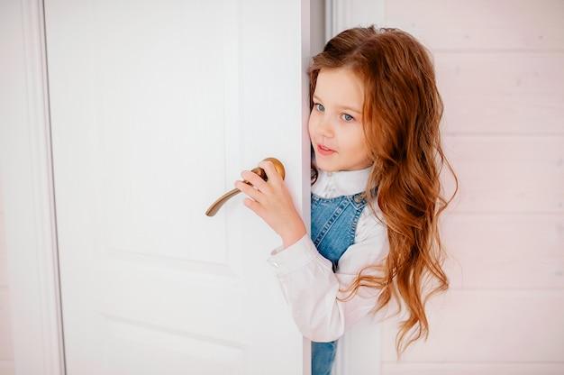 Petite fille aux cheveux bouclés jette un coup d'œil par la porte et sourit