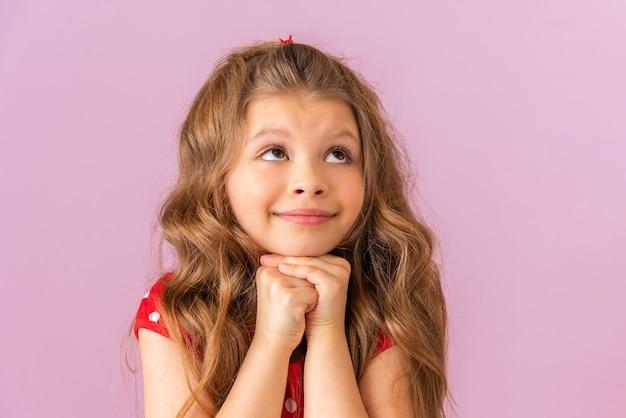 Une petite fille aux cheveux bouclés lève les yeux et rêve.