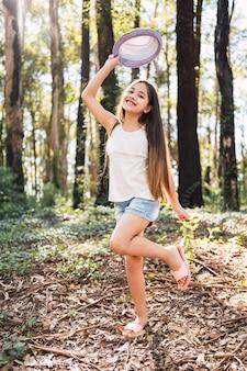 Petite fille aux cheveux longs tenant un chapeau à l'extérieur - portrait d'une jolie fille souriant joyeusement.
