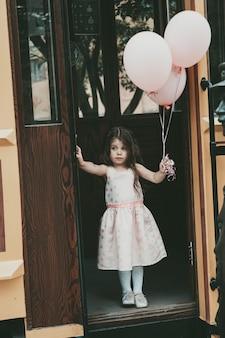Une petite fille aux cheveux longs vêtue d'une robe rose sort du tramway avec des ballons à la main. photo de haute qualité