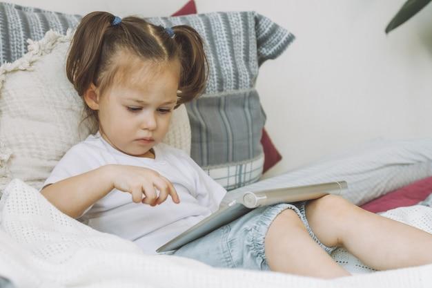 Petite fille aux cheveux noirs 2-4 avec deux queues de cheval est assise sur le lit avec des oreillers et joue à l'ordinateur tablette