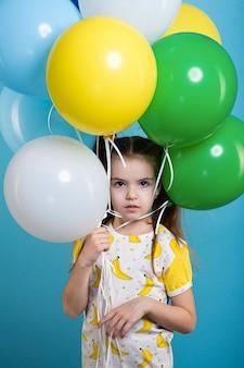 Petite fille aux cheveux noirs avec des ballons colorés sur fond bleu