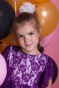 Petite fille aux cheveux noirs avec des ballons colorés sur fond rose