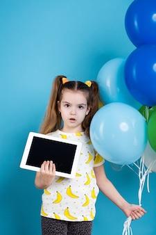 Petite fille aux cheveux noirs avec des ballons et une tablette