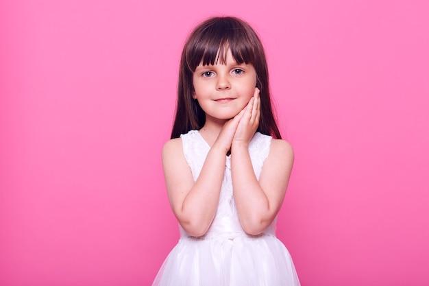 Petite fille aux cheveux noirs en belle robe blanche à l'avant avec une expression faciale calme et mignonne, gardant les deux paumes sur sa joue, isolée sur un mur rose