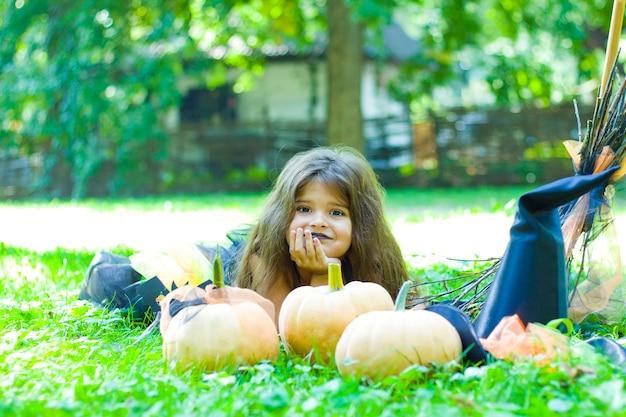 Une petite fille aux cheveux noirs en costume de sorcière est allongée sur une pelouse avec des citrouilles.