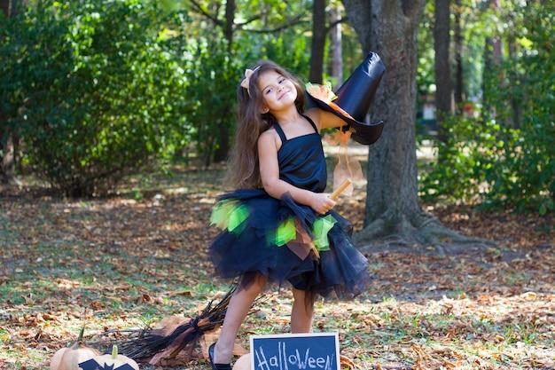 Une petite fille aux cheveux noirs dans un costume de sorcière avec un balai dans ses mains.