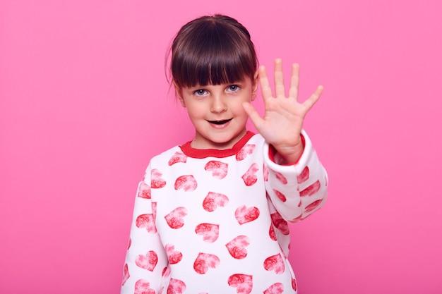 Petite fille aux cheveux noirs, montrant la paume de la main à la caméra, montre le geste d'interdiction, interdit de faire quelque chose, a une expression confiante, isolée sur un mur rose