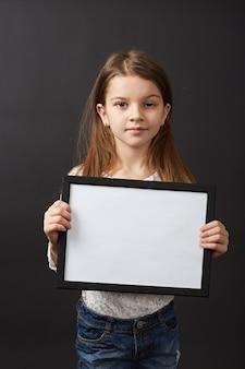 Petite fille aux cheveux noirs posant avec cadre en studio sur fond noir