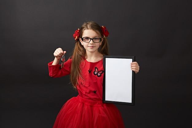 Petite fille aux cheveux noirs en posant rouge