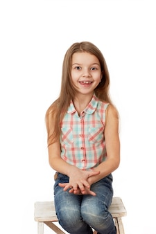 Petite fille aux cheveux noirs qui pose en studio sur fond blanc