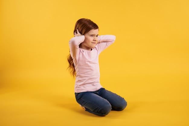 Petite fille aux cheveux rouges couvre les oreilles. extrêmement fort.