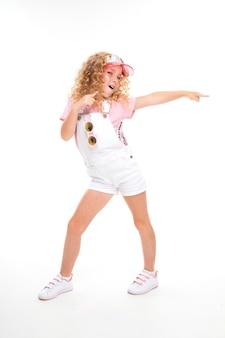 Une petite fille aux cheveux rouges dans une chemise, une combinaison blanche, des baskets blanches, une casquette et des lunettes de soleil rondes danse.