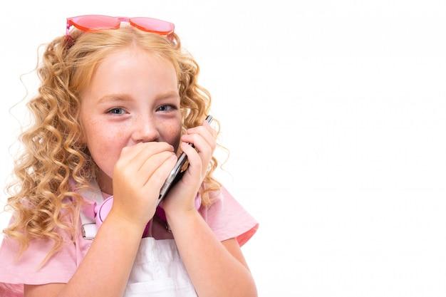 Une petite fille aux cheveux rouges dans une chemise, une combinaison blanche, des baskets blanches, des écouteurs roses et des lunettes parle au téléphone.