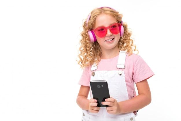 Une petite fille aux cheveux rouges dans une chemise, une combinaison blanche, des baskets blanches, des écouteurs roses et des lunettes tient son téléphone.