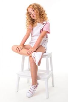 Une petite fille aux cheveux rouges dans une chemise, une combinaison blanche et des baskets blanches est assise.
