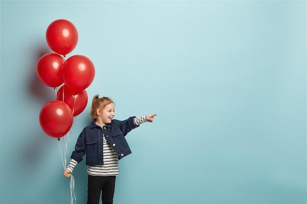 Petite fille aux cheveux rouges joyeux avec queue de cheval