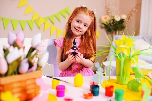 Petite fille aux cheveux rouges avec un lapin de pâques en chocolat dans les mains sur une surface de décoration de pâques