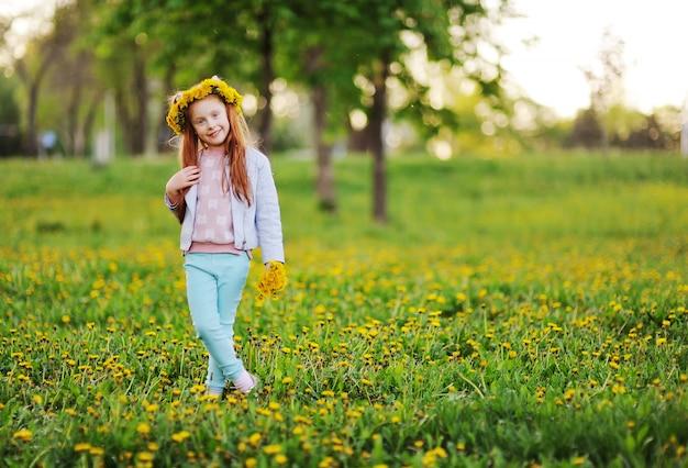 Une petite fille aux cheveux rouges sourit contre un champ de pissenlits et d'herbe verte.