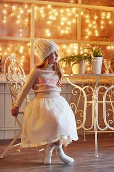 Petite fille aux cheveux roux brillant dans un chapeau blanc