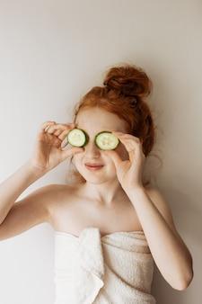 La petite fille aux cheveux roux se couvrit les yeux de tranches de concombre.