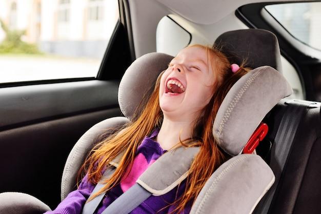 Petite fille aux cheveux roux souriante assise dans un siège auto.