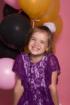 Petite fille aux cheveux sombre avec des ballons colorés sur fond rose