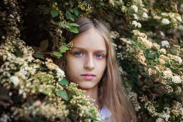 Petite fille aux longs cheveux blonds, buisson à fleurs portrait horizontal. concept de printemps.