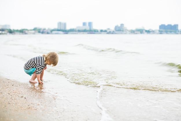 Petite fille aux longs cheveux blonds dans le vent marchant sur la plage