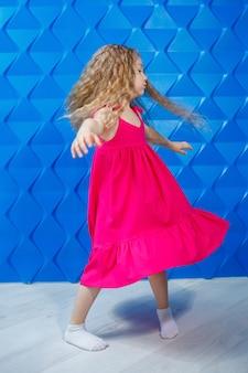 Petite fille aux longs cheveux bouclés vêtue d'une robe rose sur fond bleu danse et rit, émotions lumineuses de joie des enfants, enfance heureuse