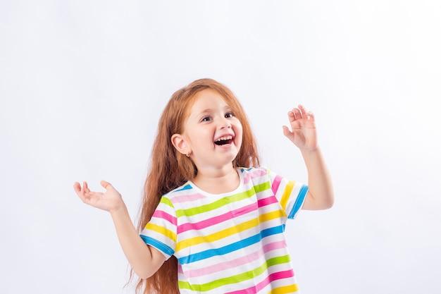 Petite fille aux longs cheveux roux sourit dans un t-shirt multicolore