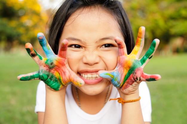 Petite fille aux mains peintes en peinture colorée