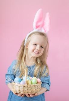 Petite fille aux oreilles de lapin debout avec un panier en bois plein d'oeufs de pâques colorés
