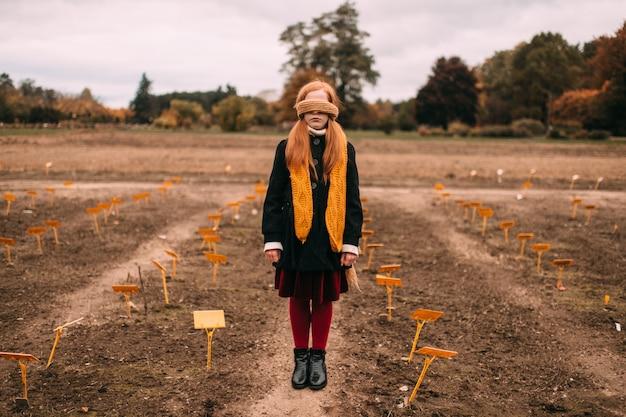 Petite fille aux yeux bandés dans l'élégant vieux vêtements façonnés debout dans le champ automne avec paysage sombre