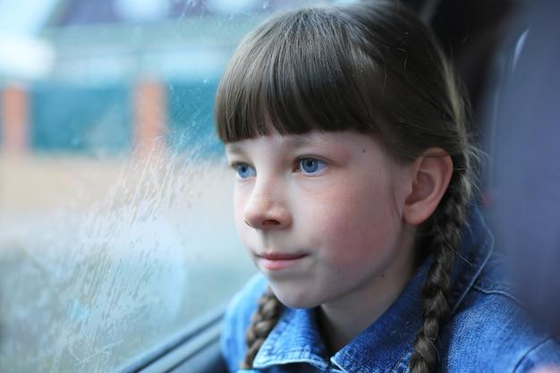 Petite fille aux yeux bleus assis à l'arrière de la voiture à la fenêtre