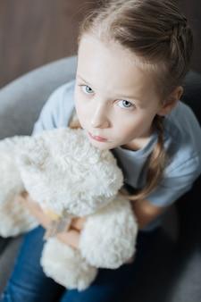 Petite fille aux yeux bleus sans sourire étreignant et tenant son ours en peluche assis dans le fauteuil