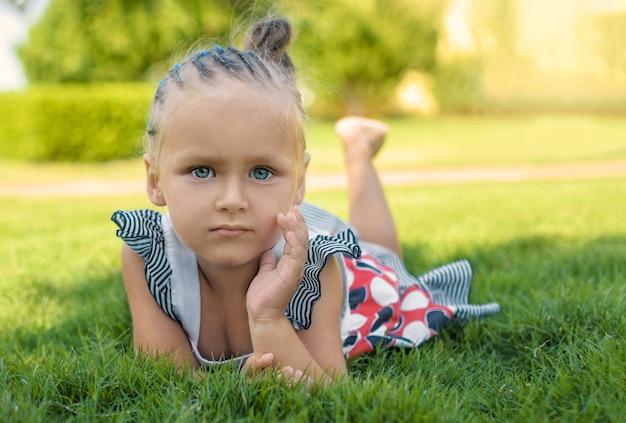 Une petite fille aux yeux brillants se trouve sur l'herbe.
