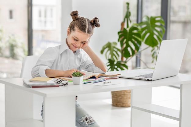 Petite fille ayant un cours en ligne à la maison