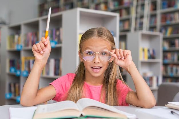 Petite fille ayant une idée dans la bibliothèque