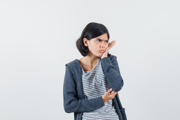 Petite fille ayant mal aux dents douloureuses en t-shirt, veste et à la recherche de mal à l'aise.