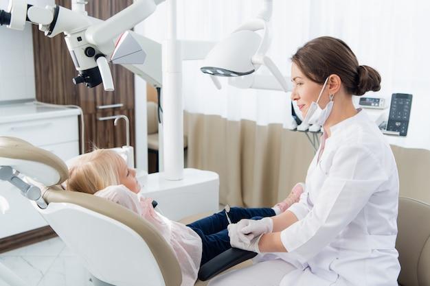 Petite fille ayant ses dents vérifiées par une femme médecin à la clinique