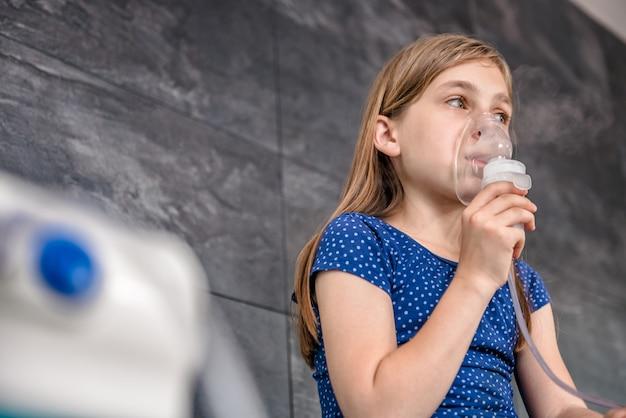 Petite fille ayant un traitement médical d'inhalation avec un nébuliseur