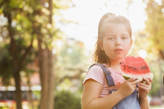 Petite fille ayant une tranche de melon d'eau
