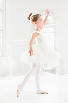 Petite fille ballerine dans un tutu. adorable enfant dansant le ballet classique dans un studio blanc.