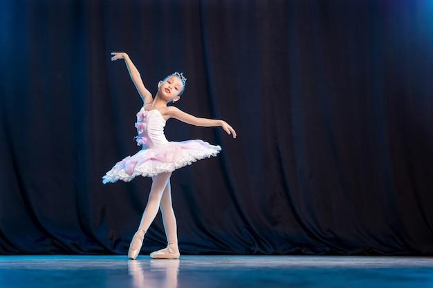 Petite fille ballerine danse sur scène en tutu blanc sur des pointes variation classique.