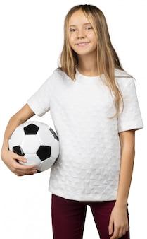 Petite fille avec un ballon de foot isolé sur un fond blanc